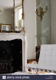 white mies van der rohe barcelona chair beside marble fireplace