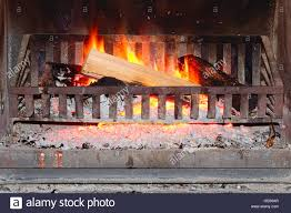 burning firewood log on metal grate in a fireplace concept of