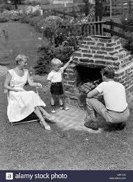 1940s 1950s family in backyard cooking hamburgers on brick