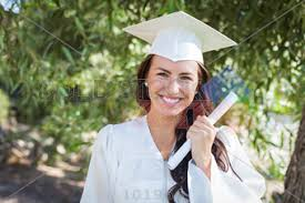 white cap and gown stock photo of prettty smiling graduate with hair