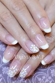 white flower nail art on a white french manicure with golden