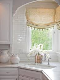a corner sink takes center stage in this white traditional kitchen