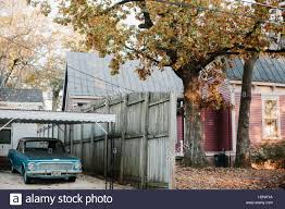 a classic american car is parked by a colourful house and autumnal