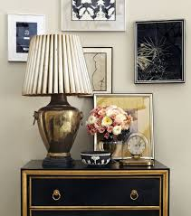 love the black and gold chest with the brass lamp and mixed framed