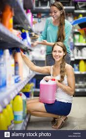 smiling spanish people buying detergents for house in the shopping