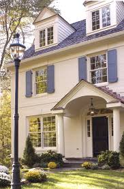 colonial house white siding stone brick blue shutters