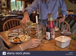man in blue shirt pouring white wine to glass during dinner in