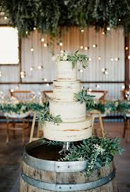 rustic wedding white wedding cake decorated with greenery brides