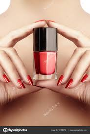 beautiful female fingers with shiny gel manicure bright red color