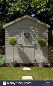 pretty wooden garden tool shed with bay standard trees either side the door with heart shaped wreath on door