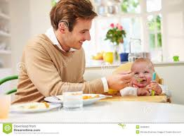 High Sitting Chair Father Feeding Baby Sitting In High Chair At Mealtime Stock