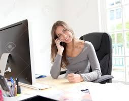 portrait of beautiful office worker sitting at her desk stock