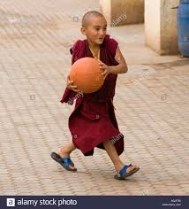 young novice buddhist monk plays basketball at the tibetan refugee