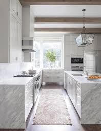 white kitchen cabinets with wood beams white kitchen with grey and white quartzite waterfall edge