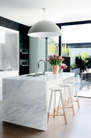 over sized pendant light over the kitchen island marble bench is