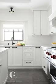 white kitchen cabinets with black hardware gray tiles cover the floors of this beautiful black and white