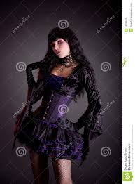 beautiful witch in purple and black gothic halloween stock