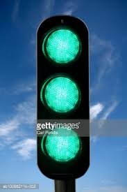 green traffic lights against blue sky closeup stock photo getty