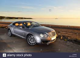 silver bentley bentley continental gt silver super car sunset next to beach