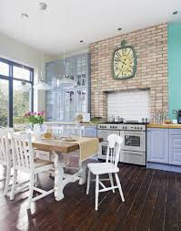 kitchen diner with blue dresser and exposed brick kitchen