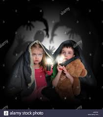 black scary halloween background two little children are hiding under a blanket looking at black