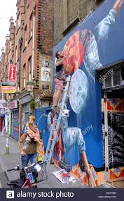 man on a ladder painting a mural on a wall a woman with child on stock photo man on a ladder painting a mural on a wall a woman with child on her shoulders walks by in shoreditch london