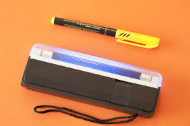 uv marker and light image of set of uv light marker device on orange background