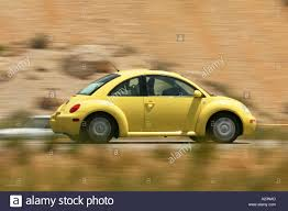 yellow volkswagen beetle royalty free yellow volkswagon beetle speeding down a road stock photo royalty