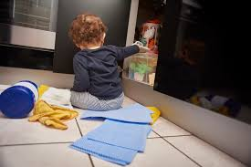 9 common safety hazards around the home how to prevent them baby boy opens up kitchen cupboard and pulls out various cleaning products from under the sink