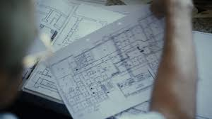 blue prints house male architect checking blueprints house construction planning