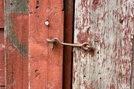 Red Barn Door by Close Up On An Antique Hook And Eye Latch Lock On An Old Rustic
