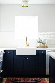 navy blue kitchen cabinets with brass hardware the kitchen reveal pre flooring the vintage rug shop