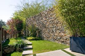 a tall stone wall framed by lush green plants and trees offers