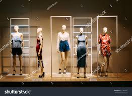 five mannequins standing store window display stock photo