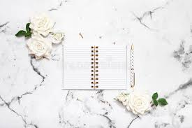 wedding planning notebook marble table flat lay with open notebook and pen for wedding