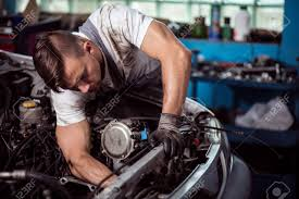 car engine service picture showing muscular car service worker repairing vehicle