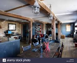 open plan living area with wooden beams and industrial lighting in