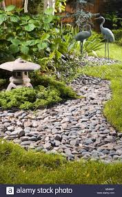 a backyard japanese garden with a dry stream bed lantern and crane