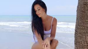 attractive middle aged women dark hair attractive woman with long dark hair sitting cross legged on sand