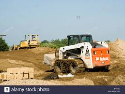 a bobcat skid loader at work on a consturction site stock photo