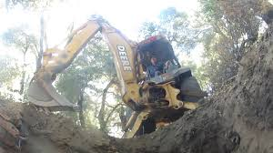 john deere backhoe digs off grid septic system in the mountains