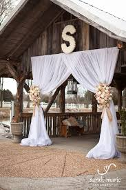 wedding arches decorated with burlap draping entrance with burlap with roses or other flowers in