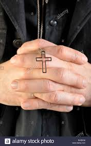 praying holding a necklace with a cross pendant stock photo