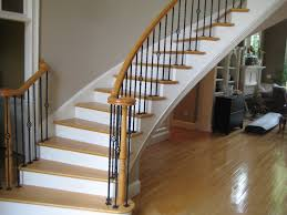 curved staircase with iron balusters and tread also wood flooring