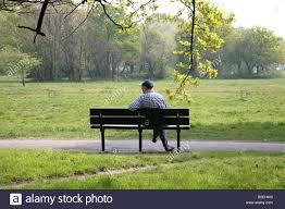 man sitting alone on park bench stock photo royalty free image