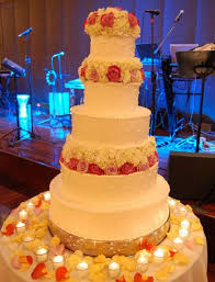 5 tier round white wedding cake with fresh flowers as toppers and