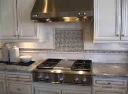 white kitchen white backsplash white granite countertop metal sink and faucet grey stone pattenr