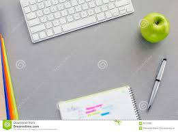 office work space on grey desk with green apple stock photo