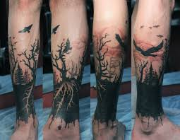 amasing black trees and swooping birds on leg tattoos