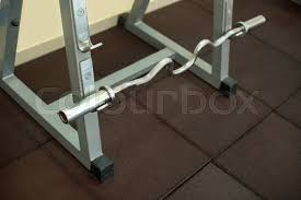 Bench Press Rack Cambered Bench Press Bar Barbell Hanging On Metal Rack In A Gym